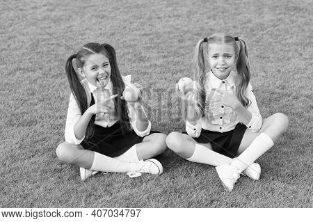 Schoolgirls Eating Apples Relaxing Schoolyard, Refuse To Eat Concept.