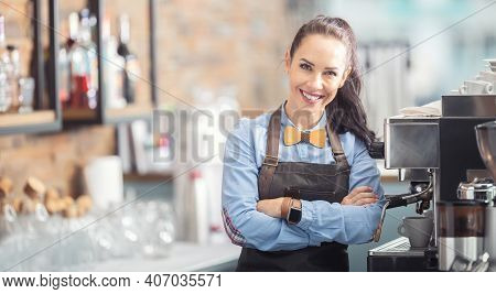 Happy Waitress In An Apron And Wooden Bow Tie Stands Confidently Next To A Coffee Maker.