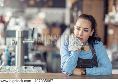Sad Female Business Owner Holds Face Mask In Her Hand And Leans Against The Bar In Her Empty Cafe.