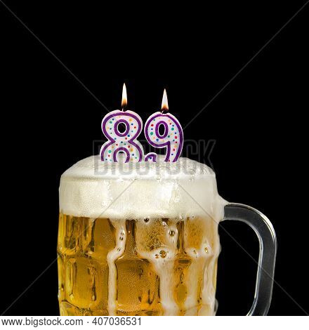 Number 89 Candle In Beer Mug For Birthday Celebration Isolated On Black