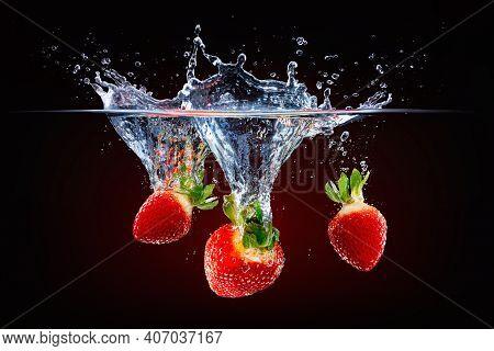 Fresh Strawberries Falling Deep Into Splashing Water