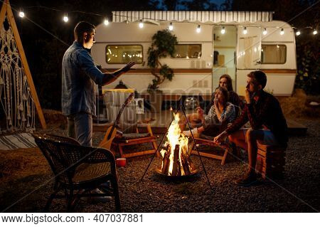 Man tells a scary story by the bonfire, camping