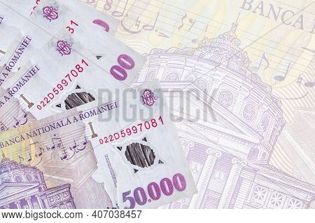 50000 Romanian Leu Bills Lies In Stack On Background Of Big Semi-transparent Banknote. Abstract Busi