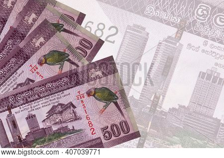 500 Sri Lankan Rupees Bills Lies In Stack On Background Of Big Semi-transparent Banknote. Abstract B