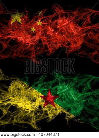China, Chinese Vs France, French Guiana Smoky Mystic Flags Placed Side By Side. Thick Colored Silky