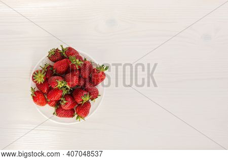 Strawberries On A White Wooden Background Top View. Red Ripe Strawberries On A White Plate. The Conc