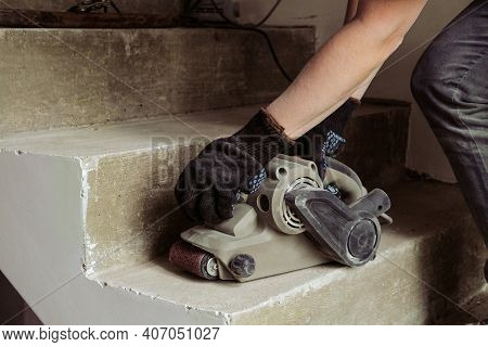 Grinding Concrete Staircase Surfaces With An Electric Sander. Worker Woman With Hand Tool Grinding M