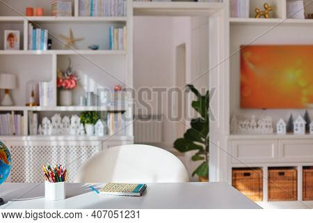 Sunlit Cozy Home Office Interior With Wooden Furniture, White Desk With Coloured Pencils