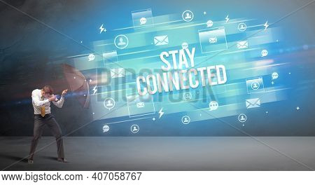 Handsome businessman defending with umbrella from STAY CONNECTED inscription, new age media concept