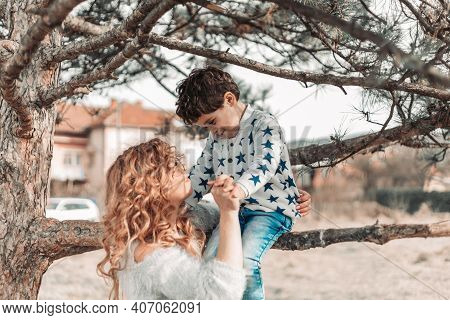 Mom Holding Her Toddler Son, While He Is Sitting On A Tree. Love And Affection