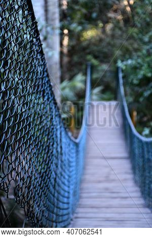 A Wooden Suspension Footbridge Has Dark Metal Mesh Railings. The Focus Is On The Foreground, With Th