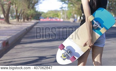 Close Up On Young Women Hand Hold Skateboard, Surf Skate On Public Park Background. Free Relax Skate