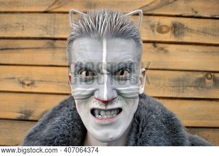 A Young Guy In Close-up In Cat Makeup, With Cat Ears And Lenses In A Gray Fur Coat Looks And Grins A
