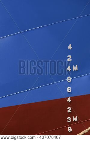 Draft Mark Numbers On Side Of Blue And Red Rust Proof Steel Hull Of Fishing Vessel In Vertical Frame