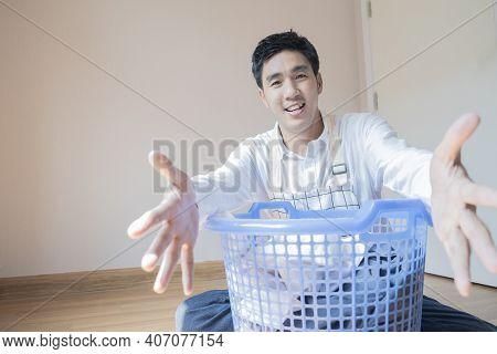 Asian Man Husband Working Homework.he Is Preparing Clothes In Basket To Wash To Washing Machine For
