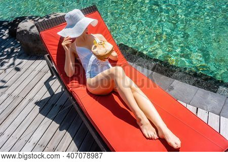 Woman lounging on swimming pool right by the water