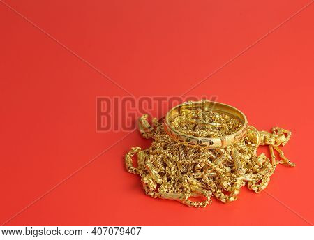 Many Gold Jewelry On Red Background With Space