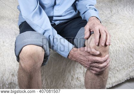 Cropped Shot Of Elderly Man Sitting On Sofa And Suffering From Pain In Knee. Joint Disease, Arthriti