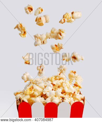 Blurred Falling Popcorns From Above In Striped Paper Bucket Of Popcorn, On Light Background.