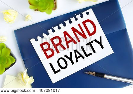 Brand Loyalty. Text On White Notepad Paper On Blue Folder. On A Light Background Near The Crumpled S
