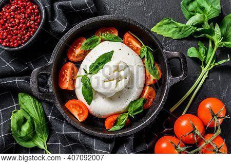 Caprese Salad With Burrata Mozzarella, Cherry Tomatoes And Basil. Black Background. Top View