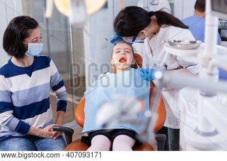 Dentist Using Modern Dental Equipment For Little Girl Treatment In Clincic. Dentistry Specialist Dur