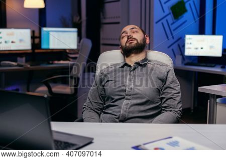 Overworked Exhausted Man Sleeps On Chair In Empty Office. Workaholic Employee Falling Asleep Because