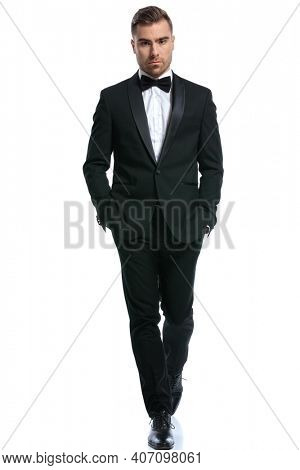 cool young businessman in black tuxedo holding hands in pockets and confidently walking isolated on white background in studio, full body picture