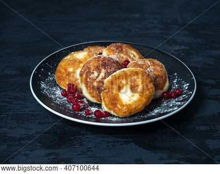 Delicious Dessert, Syrniki With Powdered Sugar And Red Currant Berries, Serving On A Black Kerpmic P