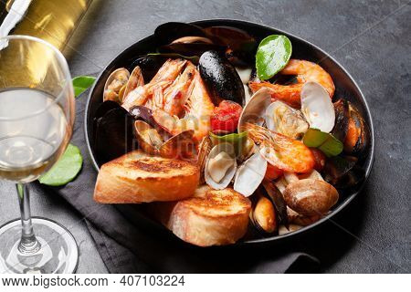 Mixed grilled seafood. Various roasted shrimps, mussels and shellfish in frying pan and white wine