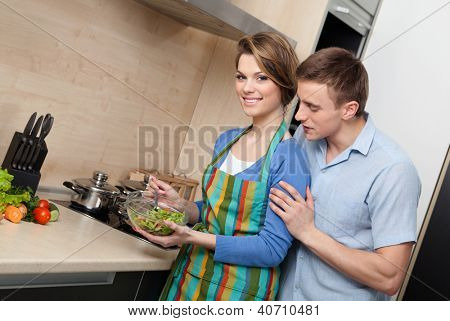 Attractive woman offers her husband to taste salad in the modern comfortable kitchen