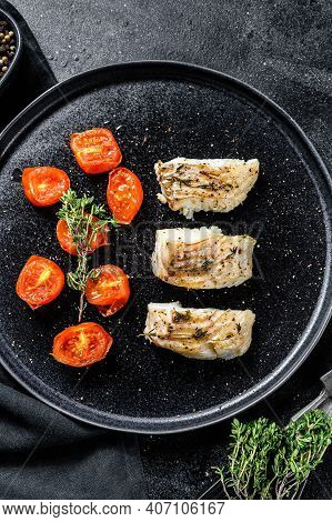 A Portion Of Grilled, Baked Pollock Or Coalfish Fillets. Black Background. Top View