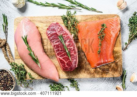 Different Types Of Raw Meat On Cutting Board With Herbs. Beef Top Blade, Salmon Fillet And Turkey Br