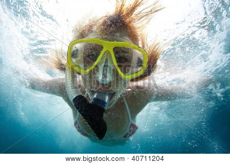 Close up underwater portrait of a woman making skin dive with a lot of bubbles on face