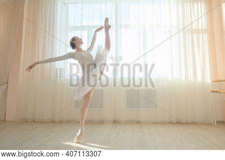 Beautiful Ballerina In Body And White Tutu Is Training In A Dance Class. Young Flexible Dancer Posin