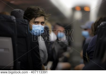 Man Wearing Medical Face Mask Inside Airplane During Flight To Protect Against Coronavirus. New Norm