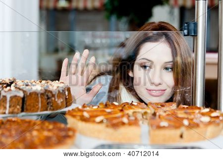 Lady in scarf looking at the bakery window full of different pieces of cakes