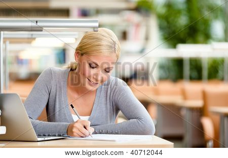 Female student studying on the laptop sitting at the desk. Process of studying
