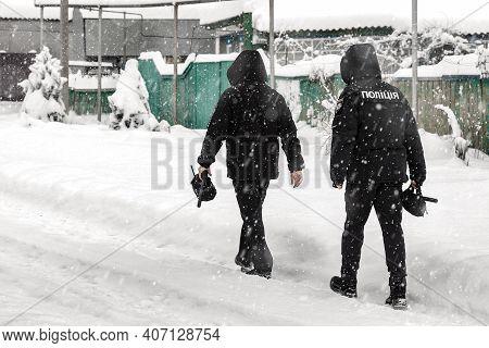 Two Ukrainian Policemen Walk A Village Street In Snowy Weather. Ukrainian Police.