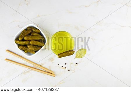 Pickled Cucumbers In A Bowl And Pickle Juice In Glass On A Light Background. Homemade Fermented Or M
