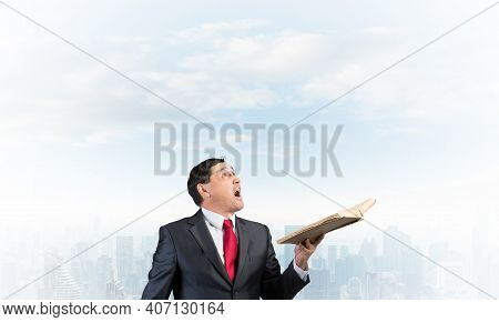Surprised Businessman Holding Open Old Book And Looking Up. Startled Adult Man In Business Suit And