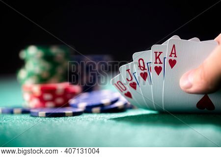 Playing poker in a casino holding winning royal flush hand of cards concept for gambling, betting and winning