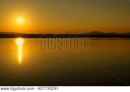 Summer landscape. Summer sea sunset landscape. Summer sea water surface lit by sunset light. Summer sunny water scene in picturesque tones. Sea summer nature with mountains at the horizon