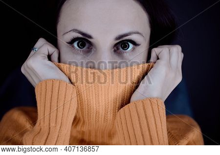 Close Up Portrait Of A Young Scared Woman With Half Face Tighting Pullover. Portrait Of A Young Woma