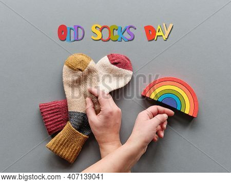 Odd Socks Day. Hand Hold Pair Of Mismatched Socks. Wooden Rainbow, Toy Figures. Social Initiative Ag