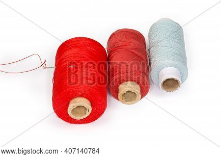 Spools Of Threads Different Colors And Self-threading Hand Sewing Needle With A Tucked Red Thread Is