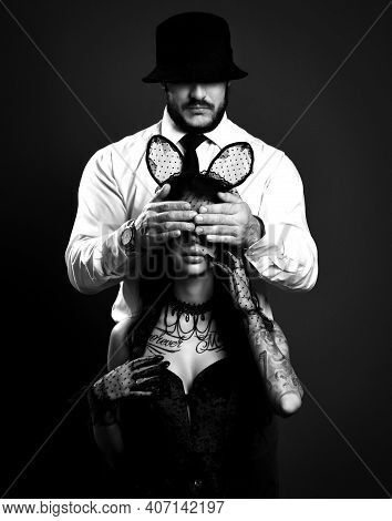 Black And White. Woman With Tattoo In Lingerie And Sexy Rabbit Mask Sits With Man In Suit Behind Her