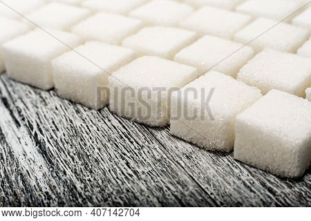 Sugar. Loose Sugar Lies In A Row On A Wooden Background. Lump Sugar In The Form Of Cubes.