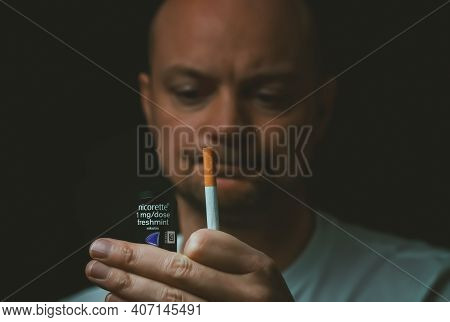 Man Holding Up A Cigarette And A Nicotine Spray, Considering Quitting Smoking. Shallow Depth Of Fiel