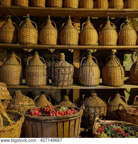 Wine bottles on shelves and baskets with grapes in wine-cellar